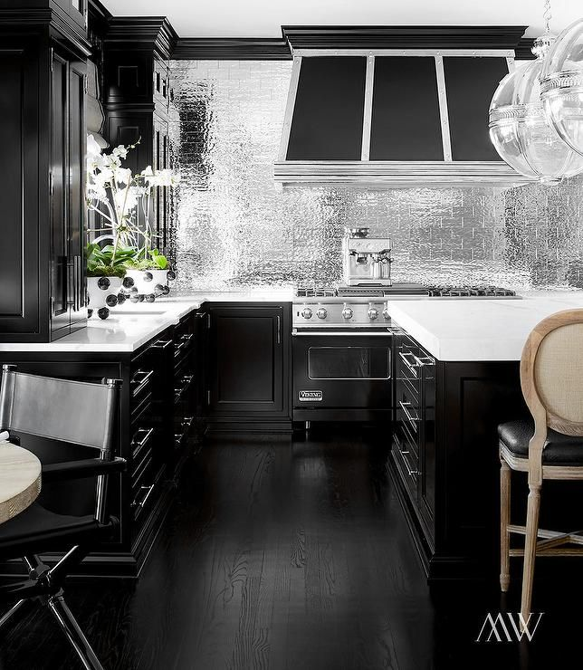 Black Kitchen Features Black Cabinets Paired With White Marble Countertops  And A Silver Subway Tile Backsplash.