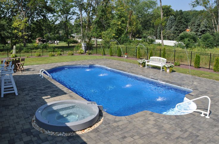 In Ground Pool Featuring A Vinyl Liner Spa Deck Jets And Hardscape Patio And Fencing