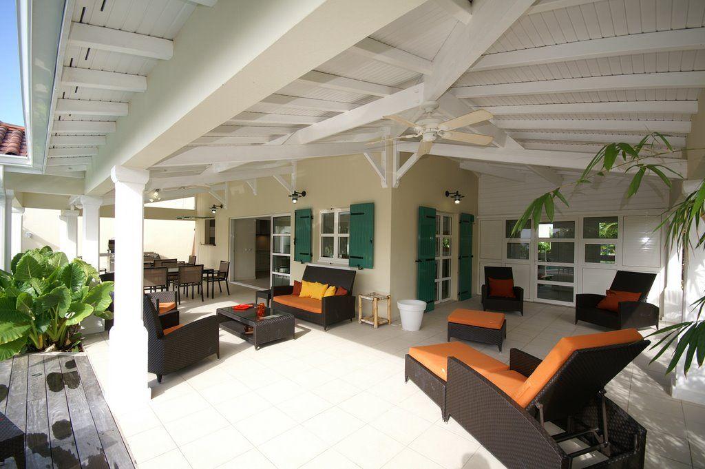 Salon extérieur et transats sous la terrasse couverte de la villa en