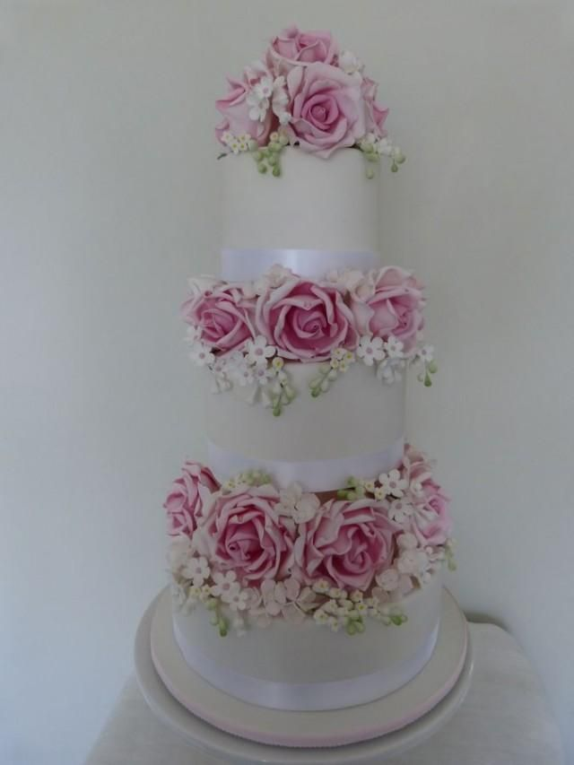 Stunning Wedding Cake featuring  roses, lily of the valley, hydrangea and white with pink fantasy filler flowers