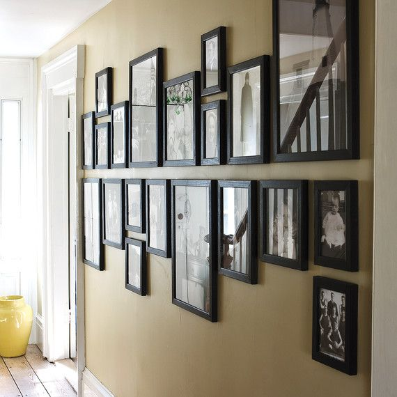 In this setting, a set of family photographs are unified with identical black frames. The arrangement trick further elongates the length of the wall: Mark a horizontal midline on the wall, and hang all of the pictures above or below it.
