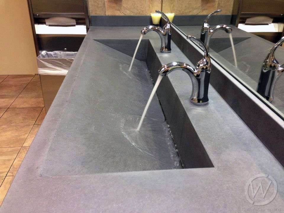 Concrete gray trough sink with double faucet and slot drain