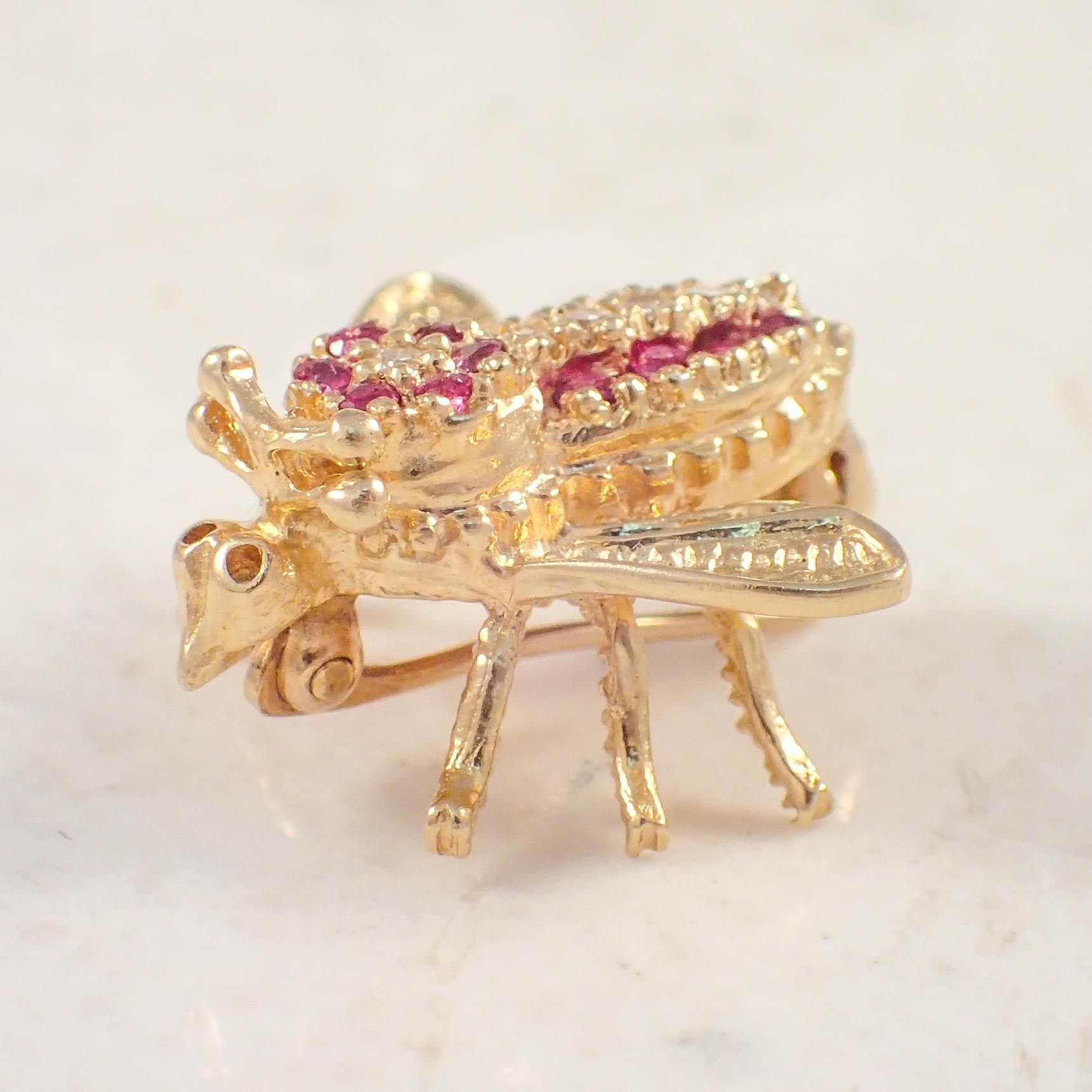 14K Yellow gold ruby and diamond bee brooch. The bee brooch is set with a row of 6 small round diamonds weighing approximately .10 carat total,