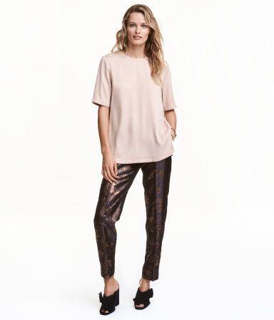 Mørk blå/Bronse. En bukse i jacquardvevd kvalitet med metallictråder. Buksen har elastikk i midjen og press. Rett passform med avsmalende ben. Sidelommer og