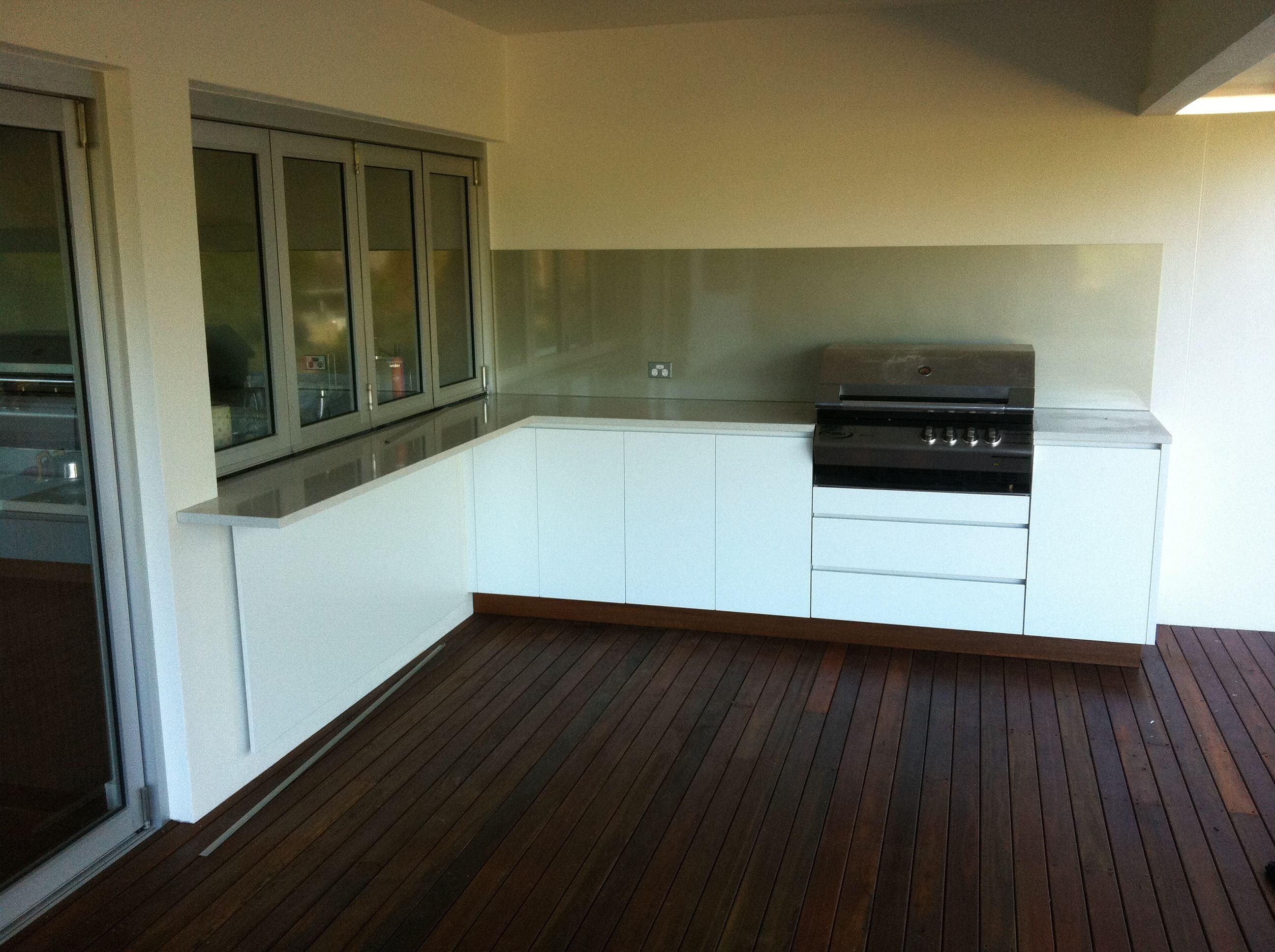 white outdoor kitchen with blue glass splashback indoor outdoo