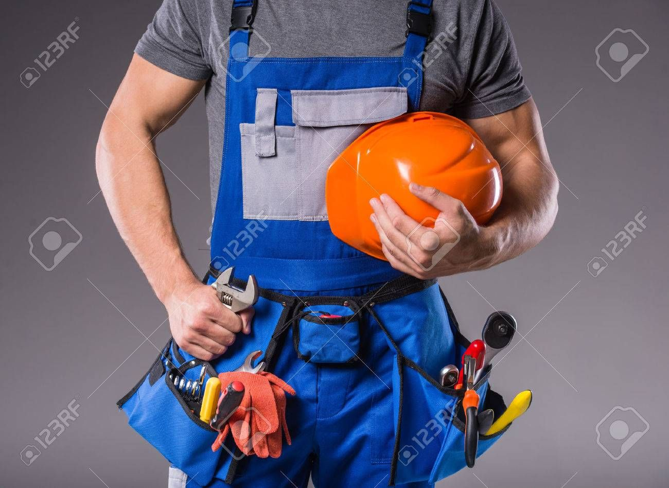 Construction Work Portrait Of A Young Builder With Tools In Hand