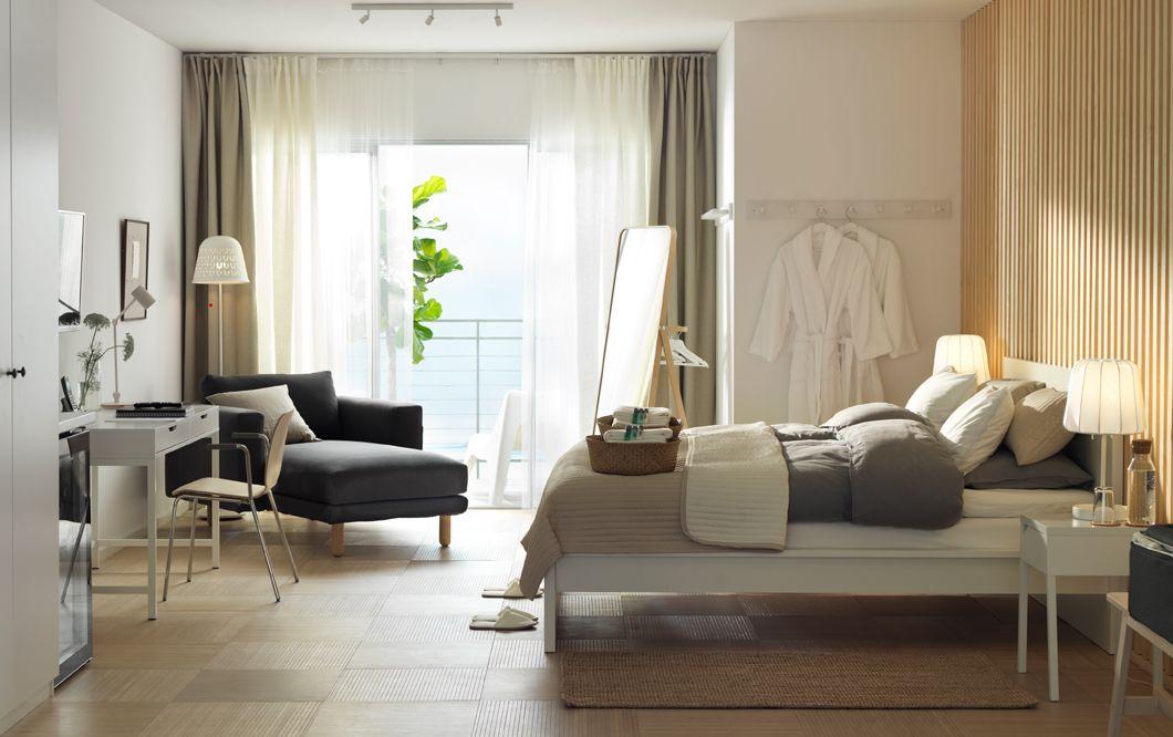 Chambre dhôtel blanche et en bois avec un lit bureau des chaises