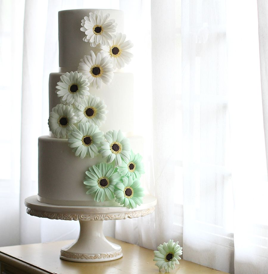 Gorgeous tiered wedding cake with green sugar daisies top