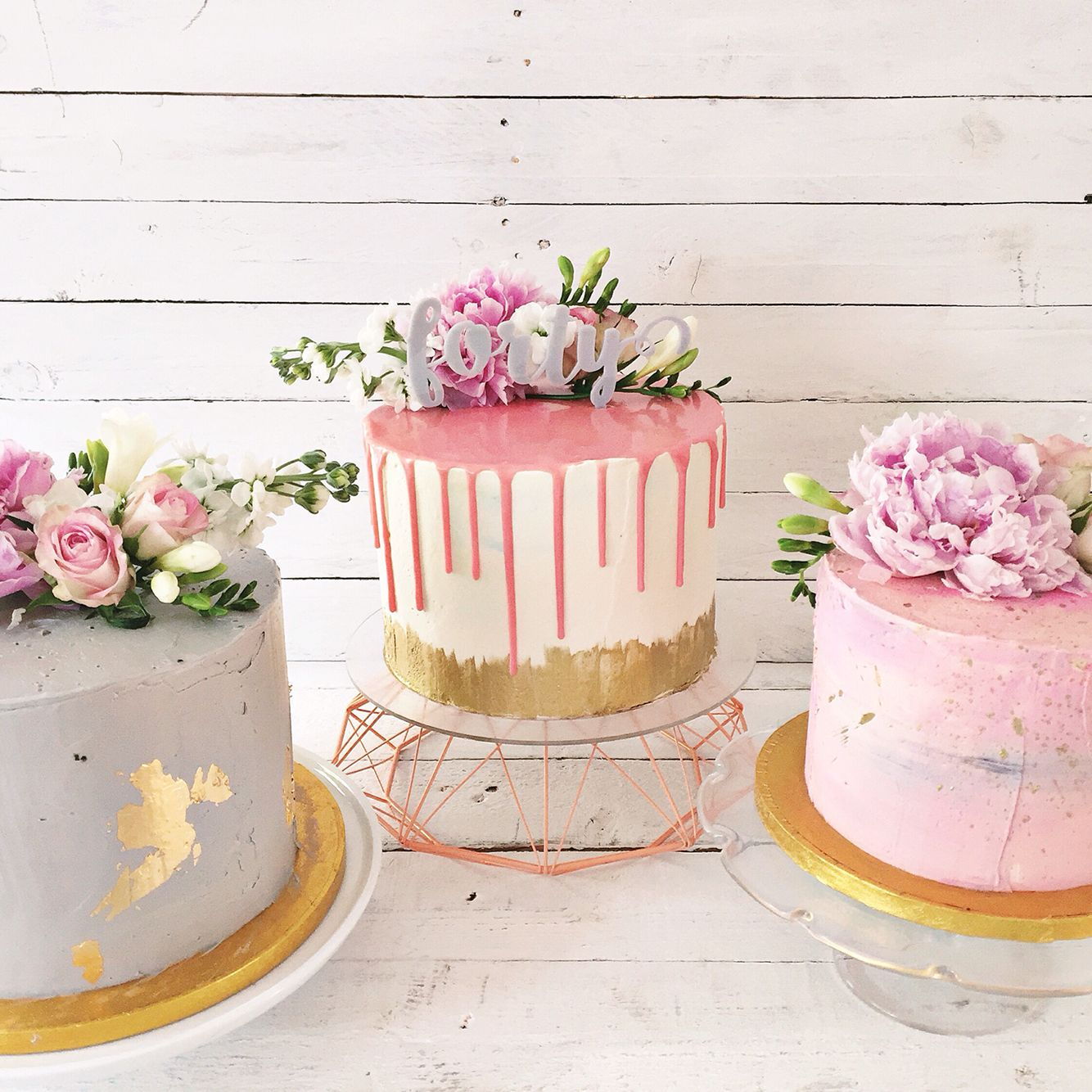 Trio of pink gold and grey buttercream birthday cakes with fresh
