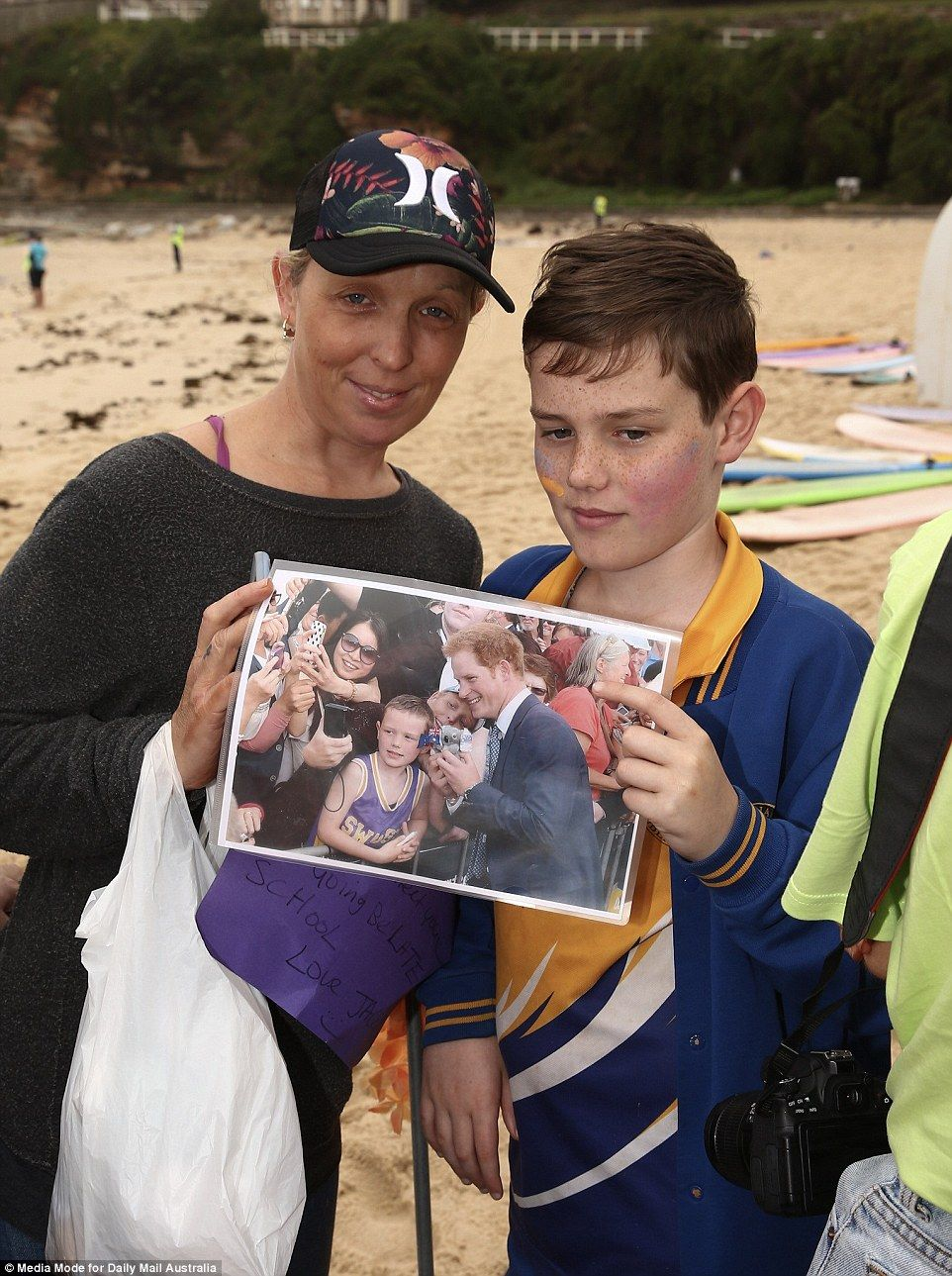 68396d9fe ... kick off shoes on beach. Jacob Andrews is pictured holding a photograph  of himself as a seven-year-old when he met Prince Harry at Circular Quay