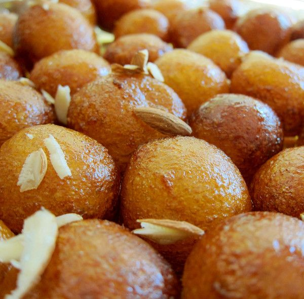 Gulab Jamun Recipe...this Indian dessert features fried dough balls soaked in a sugary syrup and topped with sliced almonds