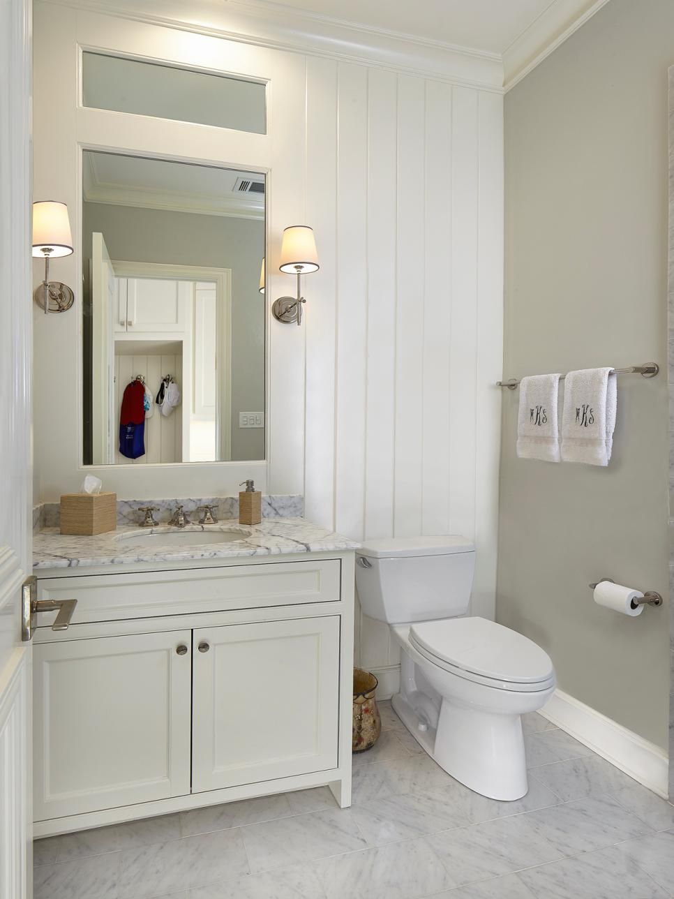 This traditional guest bathroom features white wall paneling and an ...