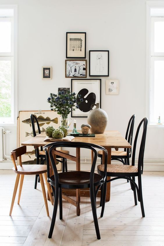 A Wonderful Dining Area With A Large Wooden Table And Black Chairs