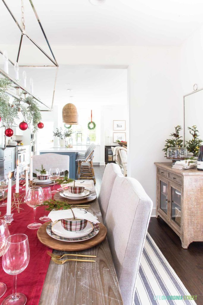 A red plaid Christmas dining room with linen chairs and reclaimed wood dining table. I love the wood chargers, plaid dishes, and gold flatware! #christmasdecor #christmashomedecor
