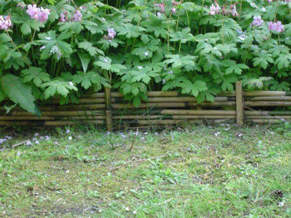 Bordure de bambous empil s entre des piquets en bambou for Bordure de jardin en bambou