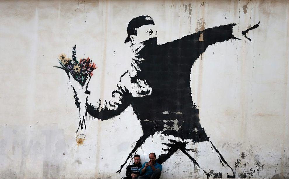 <p>POLITISK UTTRYKK: To menn sitter foran et kjent maleri av Banksy på en…