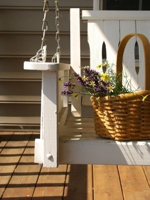 White wooden porch swing holds basket of flowers