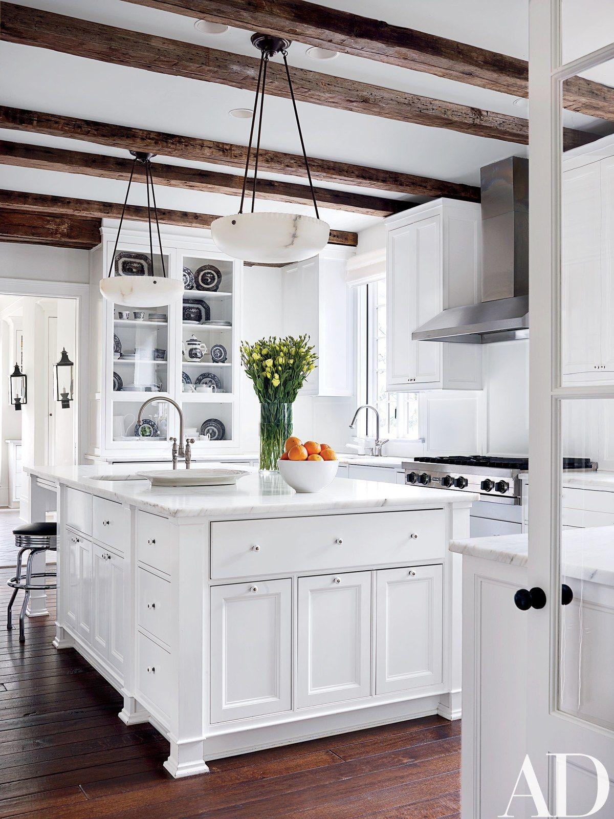 Reclaimed-oak beams shelter the kitchen, which is equipped with a Viking hood and cooktop and Calacatta gold marble counters; the alabaster pendant lights are by Urban Archaeology, and the walls and cabinetry are painted in a Darryl Carter white for Benjamin Moore.