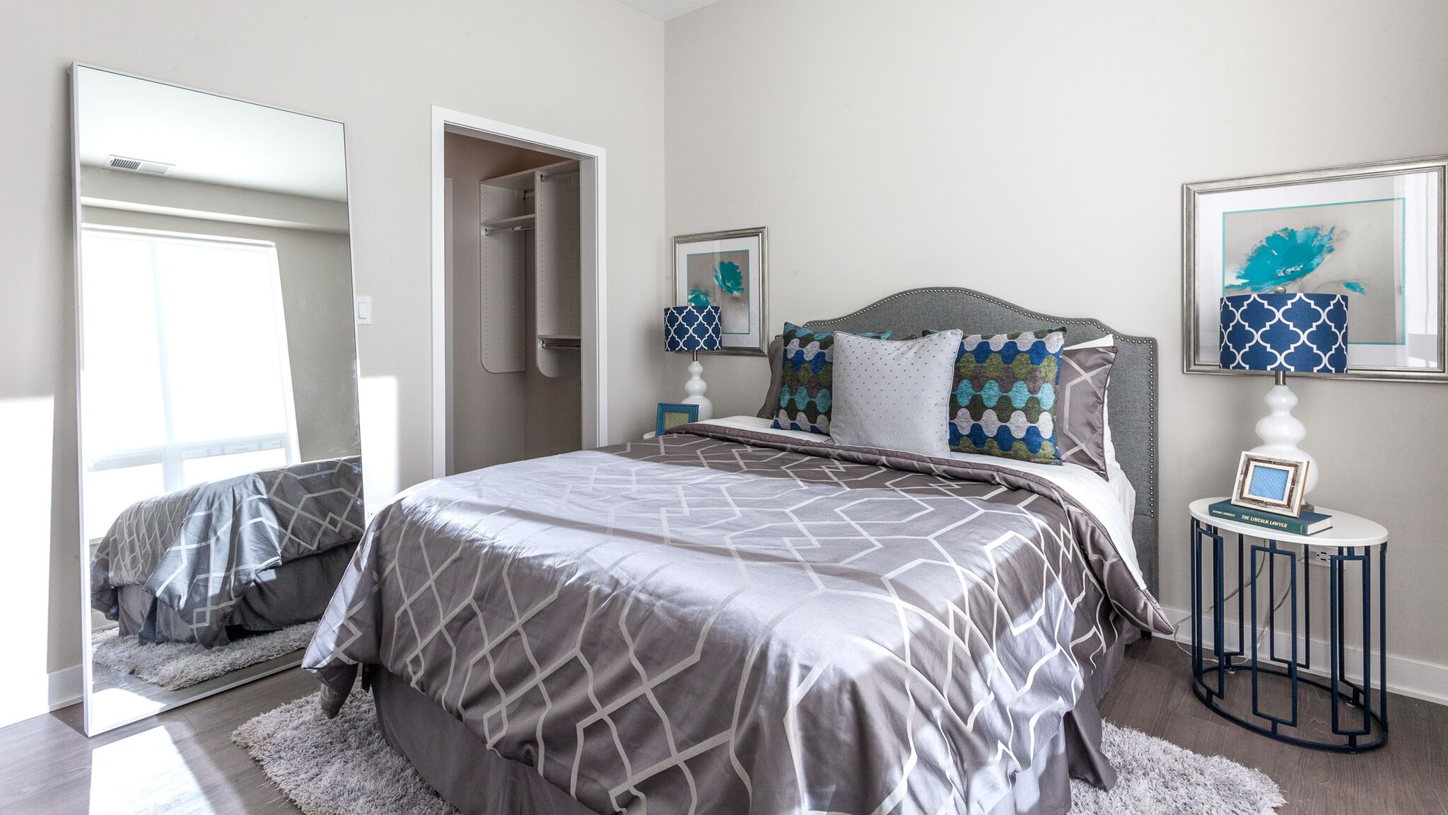 Large apartment bedroom with king size bed grey linens grey fabric