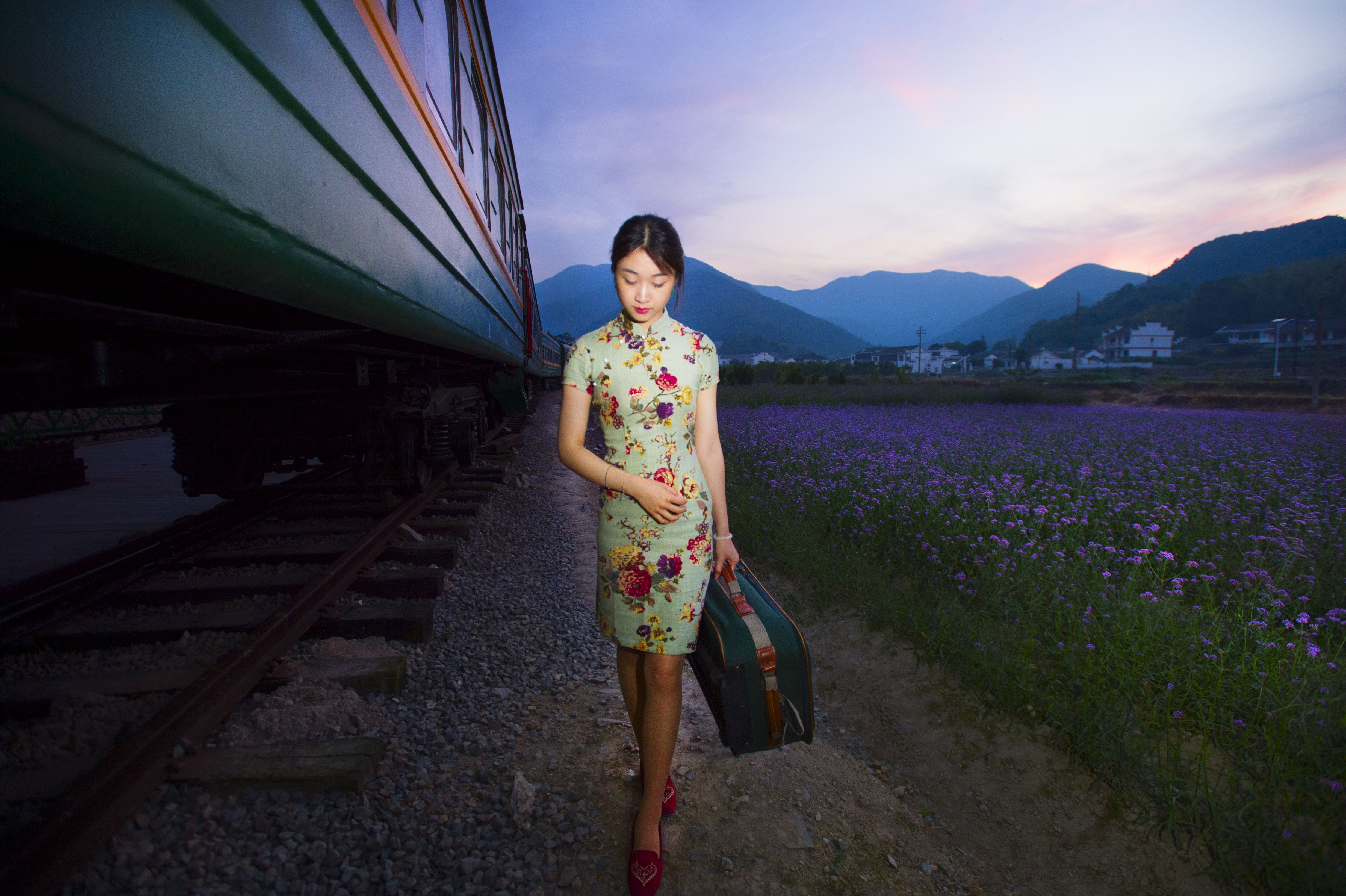 Young woman carrying luggage in old retro vintage train REDTEA