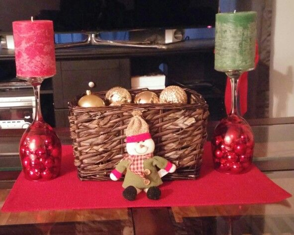 Red wine glasses with tiny red and gold ball ornaments. Christmas scented pillar candles on top of glasses. Brown wicker baskets with gold ball ornaments and cinnamon scented pine cones underneath ...merry Christmas Eveeyone!!