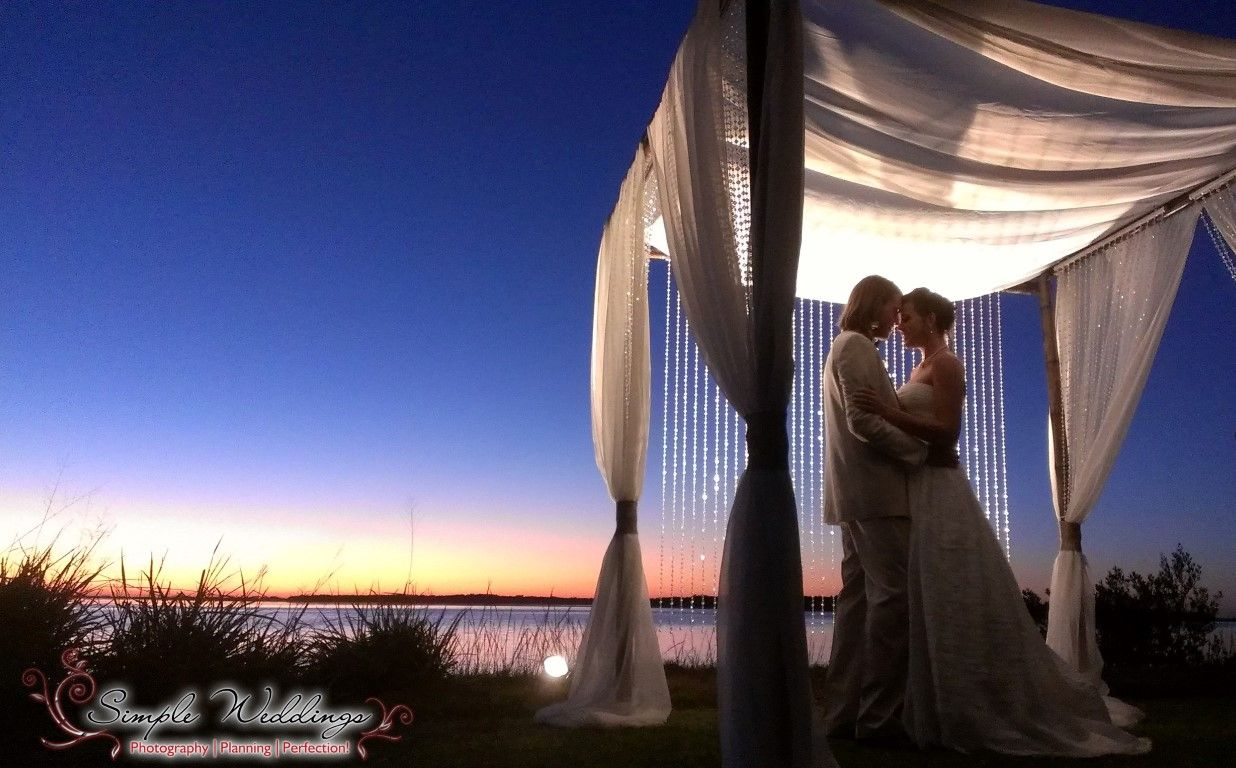 Bride And Groom Under The Lights Of Our Bamboo Canopy For A Waterfront Sunset Wedding At