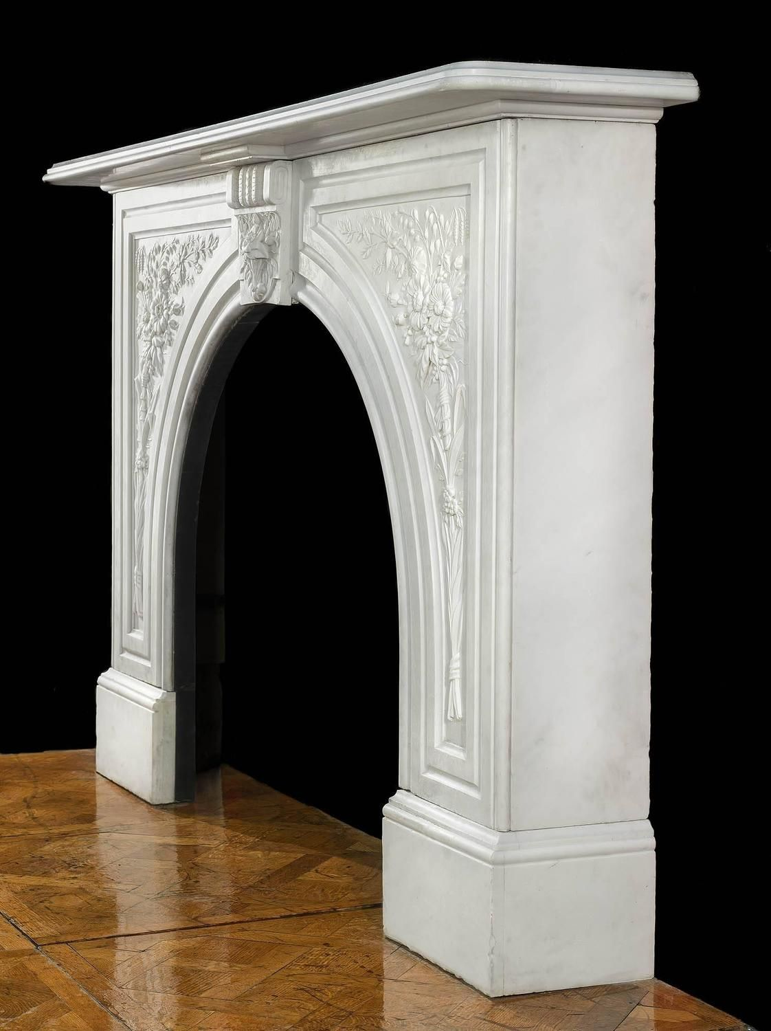 An attractive Victorian arched white marble antique fireplace surround with  a central foliate keystone flanked by large profusely carved floral  panelled ... cf09b78821