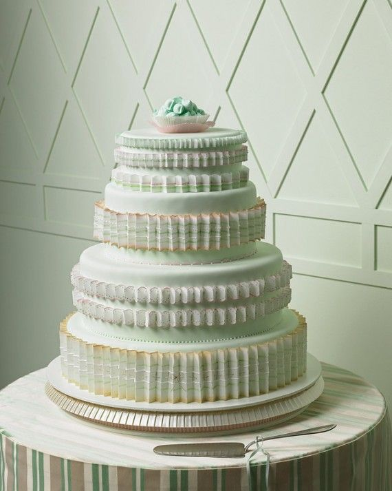 The edible pleats here recall the crinolines beneath a cream puff of a wedding dress. White wafer papers, cut with scallop scissors and folded, were painted with gold luster dust and petal dust in pinks and greens. They were then piped with white royal icing and attached to the mint-green fondant-covered tiers with more royal icing. The fluted pastry cups, filled with pillow mints, complete the pleated theme.