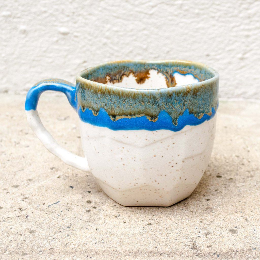 "Warm your hands on this mug with a pleasantly coarse texture. Lip features smooth ceramic glaze. Enjoy tea or coffee while daydreaming of snowy caps and crystal blue waters. Glaze pattern will vary as these are made by hand. Dimensions: 3.4"" x 3.25"""