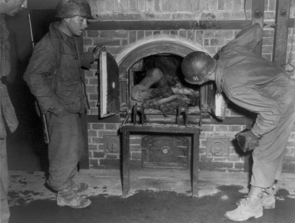American GIs examine a crematorium stuffed with several bodies at an unidentified location, 1945.