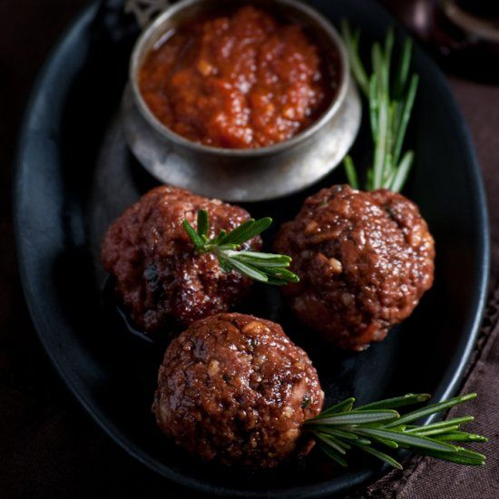 Homemade ground beef and pork meatballs served on fresh rosemary skewers.