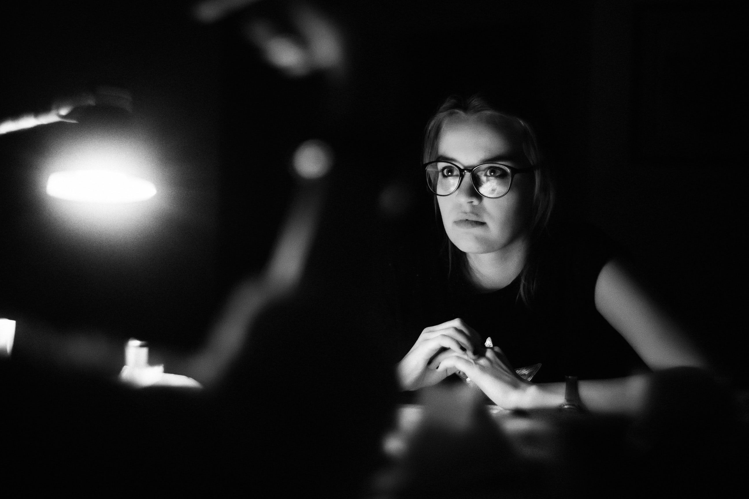 Young Woman In Glasses Concentrates In The Shadows