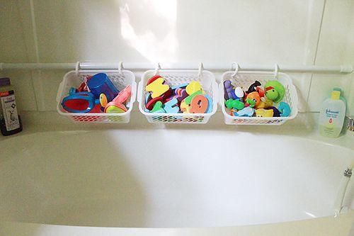 Dollar Tree plastic bins + a curtain rod = storage for bathtub toys