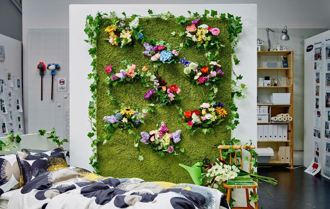 En væg dækket med et grønt tæppe, der ligner græs, og pyntet med kunstige blomster, er det perfekte indendørs blomsterarrangement.