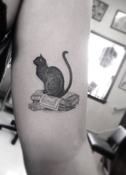 Fine Line Style Black Cat On Top Of A Bunch Of Book Tattoo On The Left Inner Arm Tattoo Artist Dr Woo Bookish Tattoos Black Cat Tattoos Cat Tattoo Designs