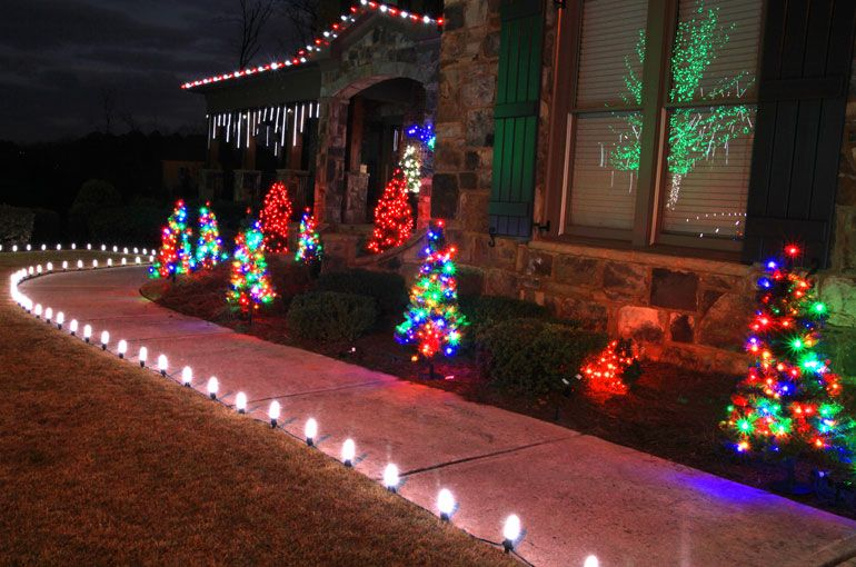 lighted led mini christmas trees staked into the front lawn walkway