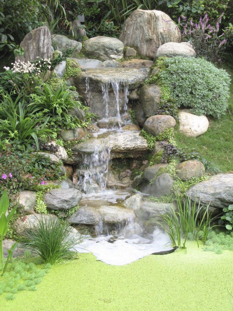 A three-tiered stone waterfall that ends in a tiny but deep well. The  ground surrounding it is covered in thick moss and algae. - 50 Pictures Of Backyard Garden Waterfalls (Ideas & Designs) GARDEN