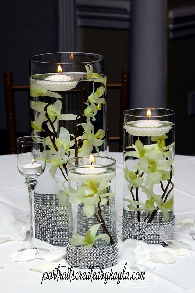 Three level clear cylinder vases with floating flowers and