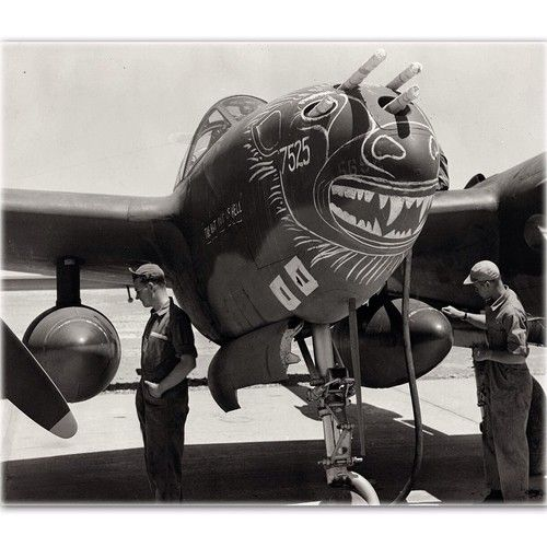 """P-38F """"The Bat Out of Hell"""" with some neat nose art in the works, while airmen inspect drop tanks. Belonging to the 12th Air Force's 94th Fighter Squadron in Tunisia, 1943."""