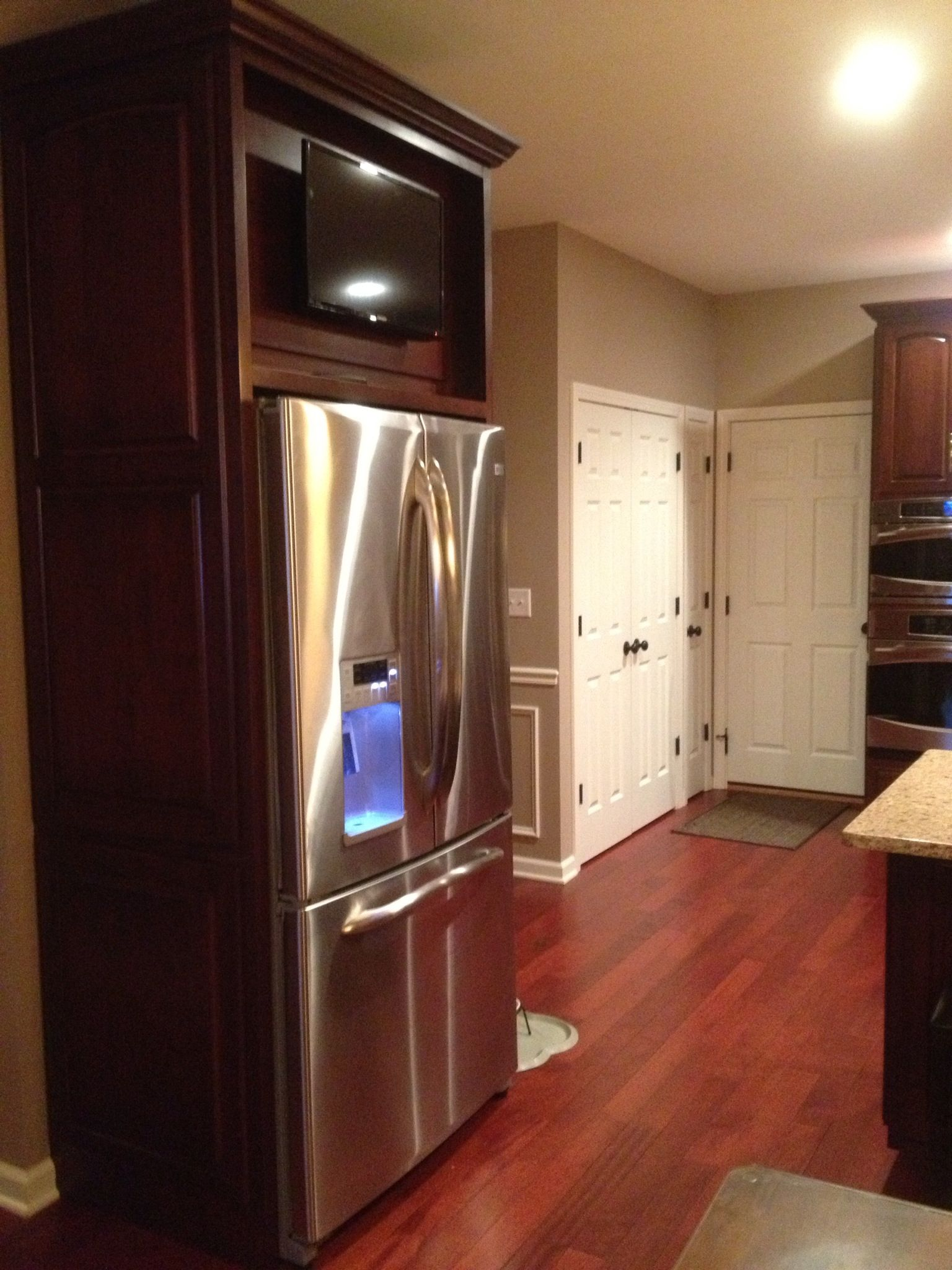 TV mounted above refrigerator on a cabinet door that is hinged ...