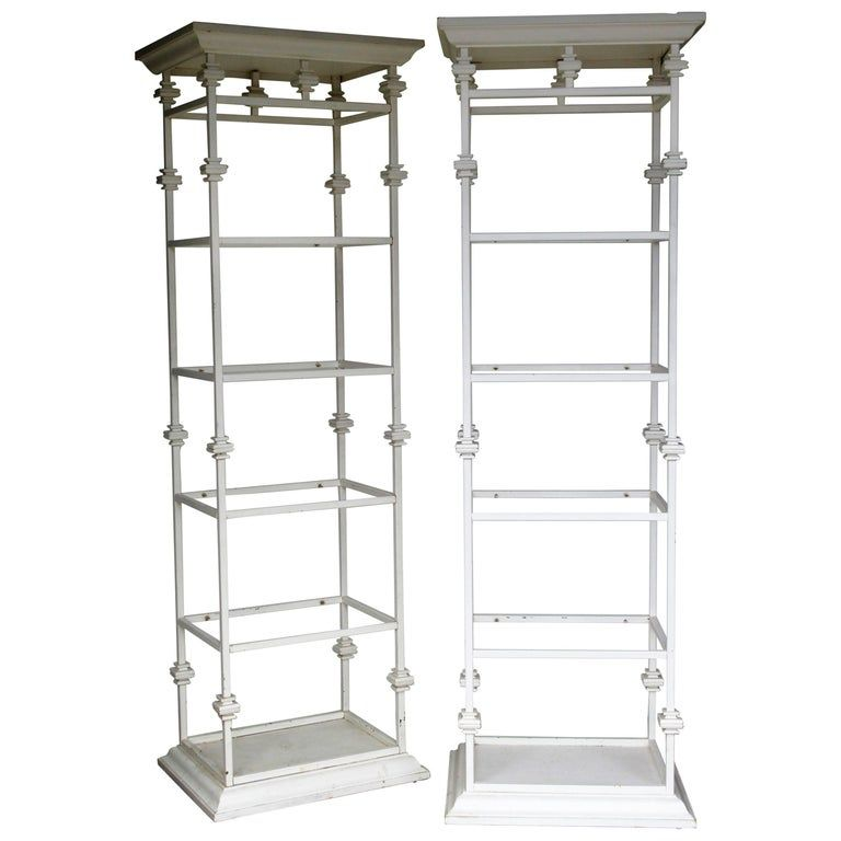Great looking pair of iron and composite Hollywood Regency classical architectural form etageres in older white painted surface. Each with four smoked glass shelves. See all pictures.