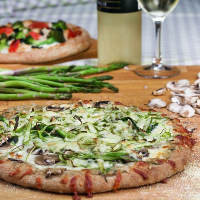 Shaved asparagus, mushrooms, bechamel sauce and a mix of mozzarella and emmenthal on top of a whole wheat pizza dough