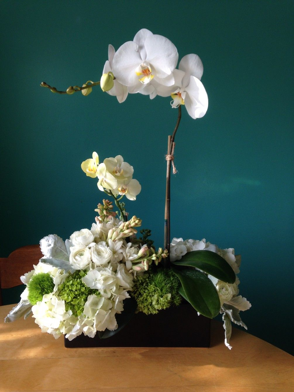 Double phalaenopsis orchid nestled in a wood box filled