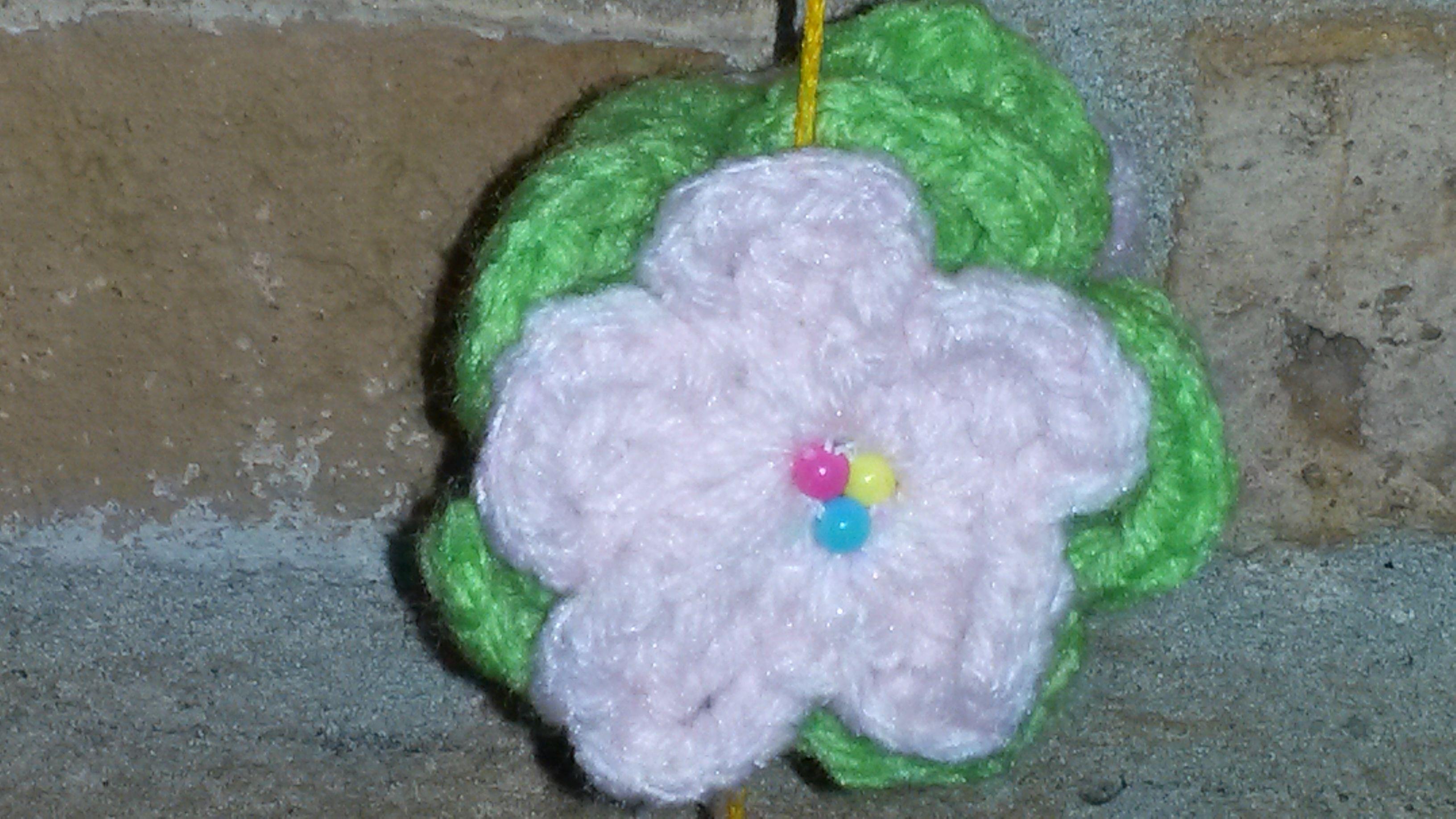 Detalle de flor tejida al crochet en lana color rosa pálido y hojas verde flúo. Doble y con centor de mostacillas.