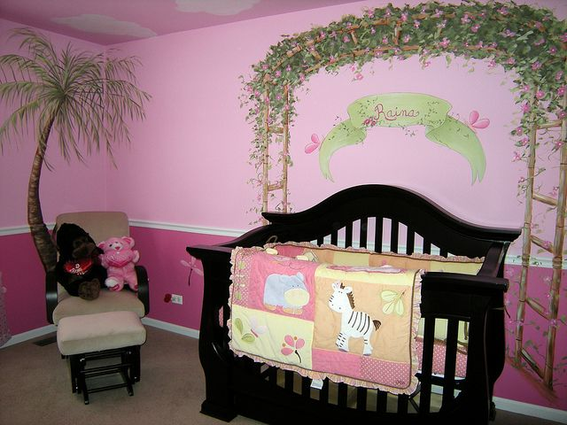 Girls love animals too! This large, pink baby nursery is filled with palm trees and sweet, safari animals including monkeys, giraffes and birds. The crib is framed by a 'bamboo trellis' covered in pink, tropical flowers. I also painted very whimsical