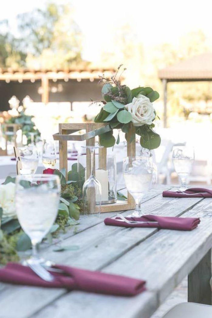 Outdoor tablescape with burgundy cloth napkins and eucalyptus table runner #clothnapkins