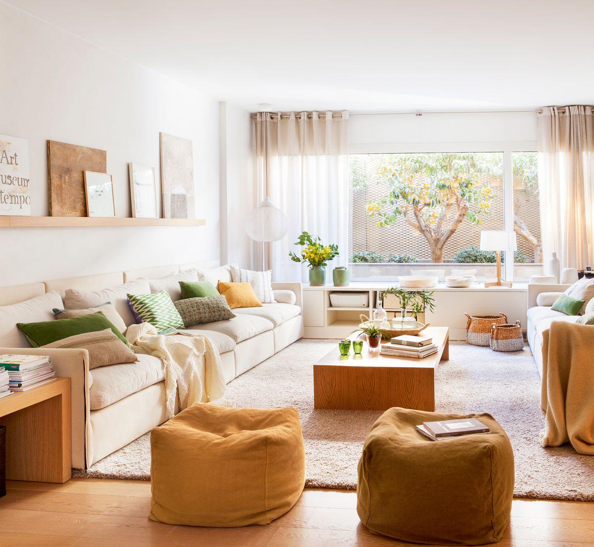 Saln con sofs claros pufs de color tierra y ocre alfombra clara