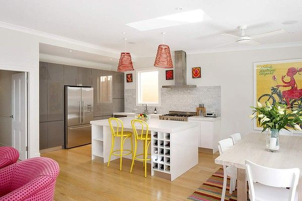 Yellow and red accents bring the open plan living area to life. The bistro stools in canary yellow are from Thonet as are the white painted timber Hermann dining chairs.
