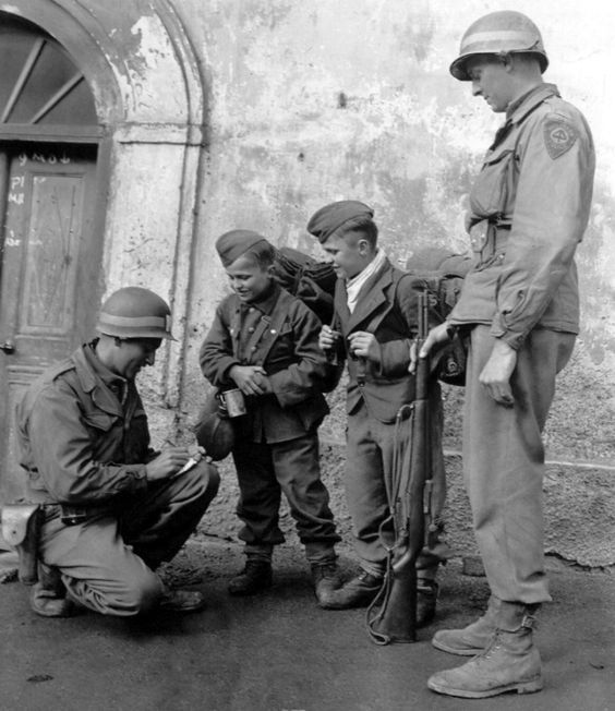 U.S. Military Police of the 44th Infantry Division interview two juvenile Wehrmacht soldiers following the surrender of divisions of the German 19th Army in western Austria. Towards the end of the war, with able-bodied German men in short supply, German and Austrian boys as young as 12 and 14 were being conscripted to fight in a last ditch effort to turn the tide of the war. Landeck, Tyrol-Vorarlberg, Ostmark (prior to the war and afterward: Landeck, Tyrol, Austria). 5th May 1945.