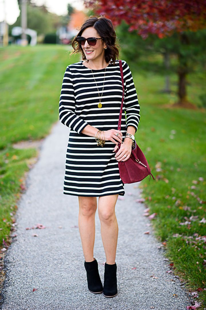 ef02b4808a How to Wear a Black and White Striped Dress Outfit for Fall: with black  ankle boots and a burgundy bucket bag